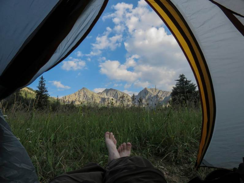 View of bare feet, meadow, and mountains from tent