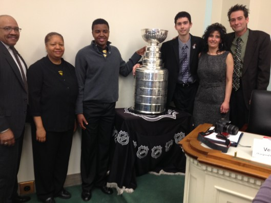 Donnie Shaw II (third from left) and Rick Lucas (third from right) huddle with their families and the Stanley Cup.
