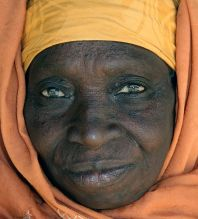 Elderly Gambian woman's face surrounded by yellow and orange hijab. January 2008, The Gambia. ( Ferdinand Reus/Creative Commons**)