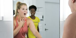 "Amy Schumer reacts to her reflection in the gym bathroom mirror with Sacheer Zamata reacting to Schumer in the background in ""I Feel Pretty"""