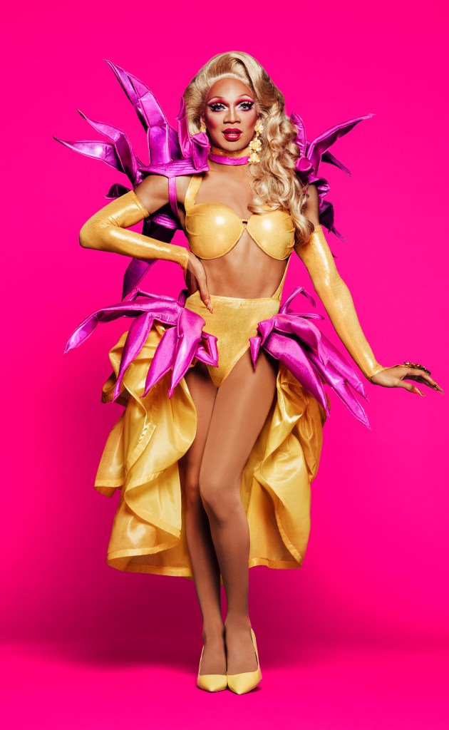 This is hard to describe, to be honest. Kahanna Montrese wears a honey blonde wig and gold-flesh colored bikini showgirl outfit with a skirt-bustle. She also has arm warmers(?) of the same color. She also has purple fabric spiky things adorning her shoulders and hips. She's wearing heels the same color as her gold outfit.