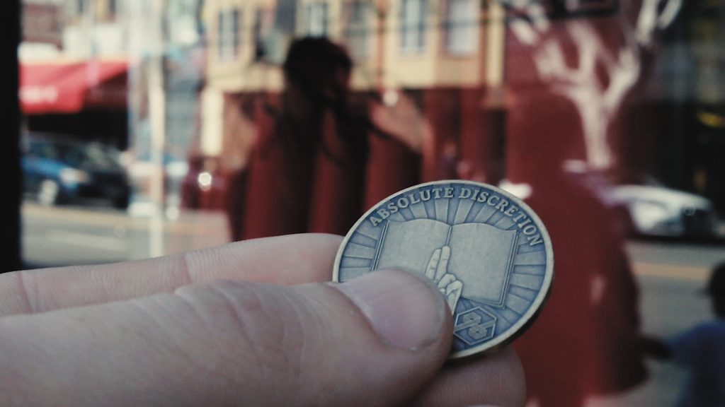 The coin every member of the House of Latitude receives upon joining the society. A scene from In Bright Axiom.