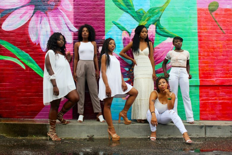 Photo of confident Black women in front of a colorful background by Clarke Sanders