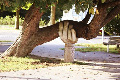 Wooden hand holding up a branch of a tree