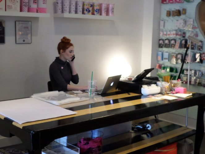Co-founder Sarah Lorsung Tvrdik taking calls while working the store.