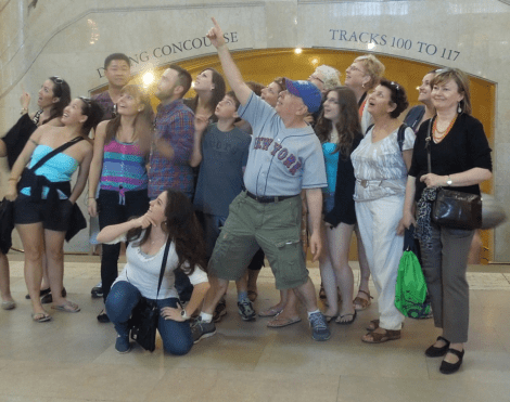 Fred Pflantzer, NYSee Tours, poses with a group he is leading through Grand Central Terminal.