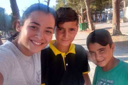 Liza Chartampila with two Syrian refugee children in Greece.