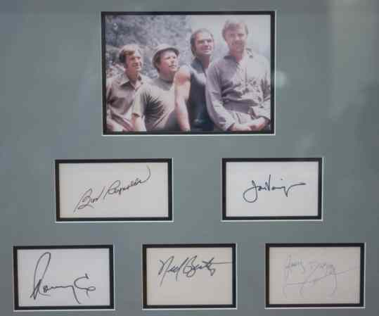 """This framed memorabilia from the set of """"Deliverance"""" includes a picture of the film's stars, from left: Ronny Cox, Ned Beatty, Burt Reynolds and Jon Voight. It is autographed by all four actors, as well as by James Dickey, who made a cameo as the sheriff in the movie."""