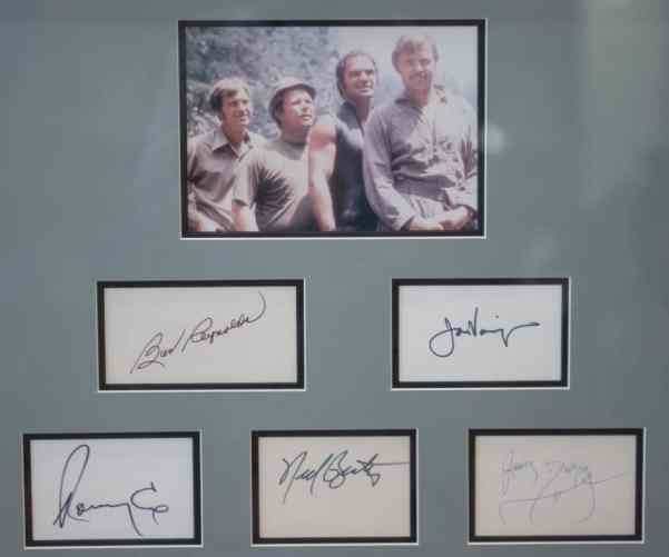 "This framed memorabilia from the set of ""Deliverance"" includes a picture of the film's stars, from left: Ronny Cox, Ned Beatty, Burt Reynolds and Jon Voight. It is autographed by all four actors, as well as by James Dickey, who made a cameo as the sheriff in the movie."