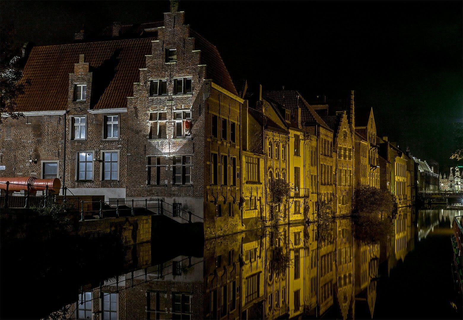 Foto van de Kraanlei, Gent in het donker. De foto is van over het water genomen. Door de lange sluitertijd spiegelen de gebouwen in het water.