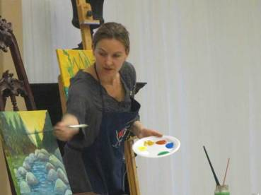 Teacher shows students the next step in creating beautiful paintings
