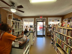 Inside a book store with shelves of books and employees working
