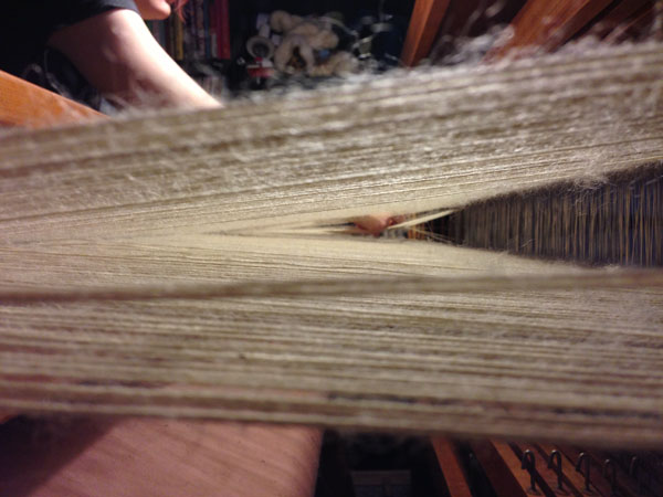 Undoing- by hand, the fuzzies that have been produced by the friction of the reed and the change of harnesses.