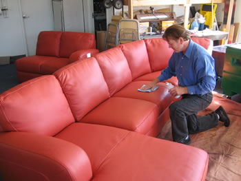 Picture showing a man cleaning his leather sofa after dying it with red color