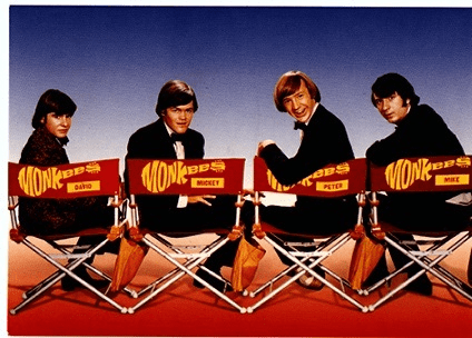 The Monkees in director chairs