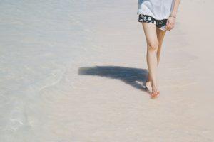 日傘をさして砂浜を歩く女性の足元