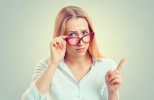 眉間にしわを寄せるメガネ女性