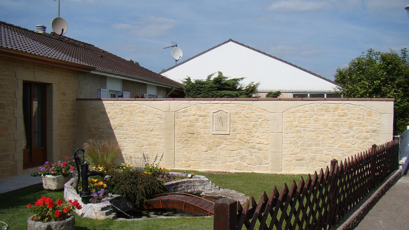 décoration en fausse pierre sur mur de séparation avec cadran solaire