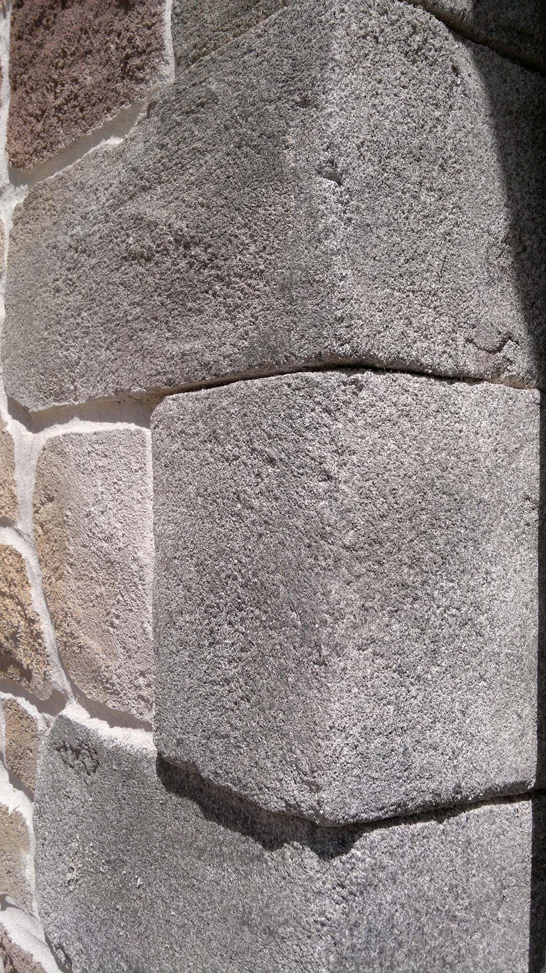 vue de près enduit fausse pierre d'angles en granit sur angle de maison