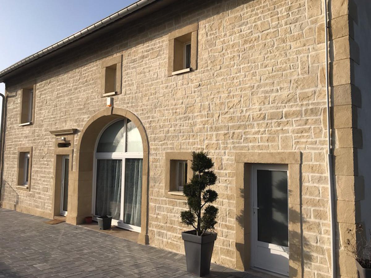 enduit fausse pierre calcaire couleur jaune pâle sur facade avec porte cochère