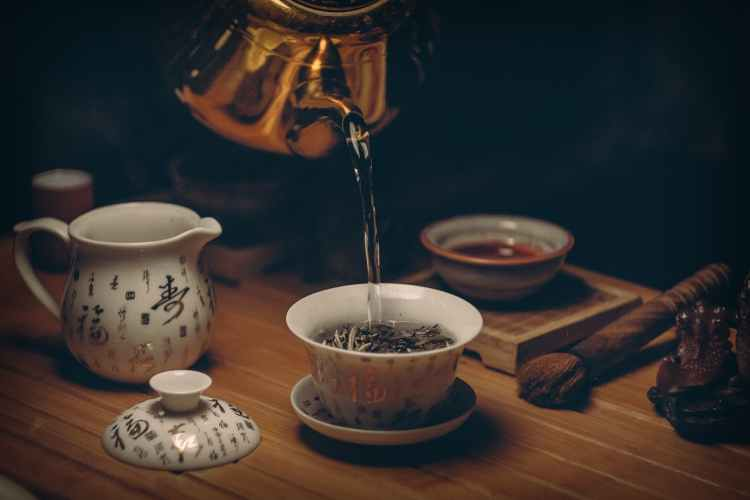 gold kettle pouring hot water on cup of tea