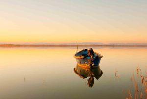 barque-eau-paisible-montagnes-au-loin-orangee