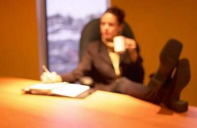 business woman sitting at desk with coffee in hand