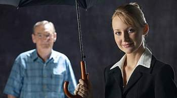 woman with umbrella and person standing in background