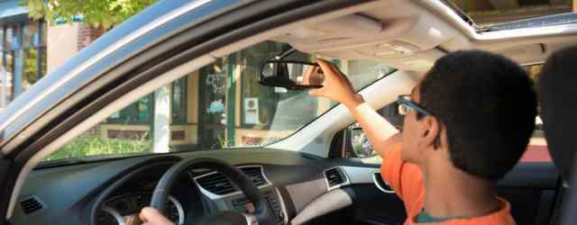 Driver adjusting their mirror