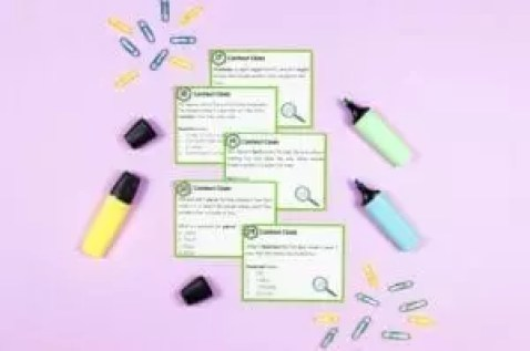 Teaching Context Clues task cards with highlighters and paper clips on a purple background