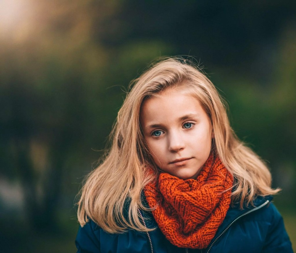 Female grade school student with blonde hair looks deep in thought.