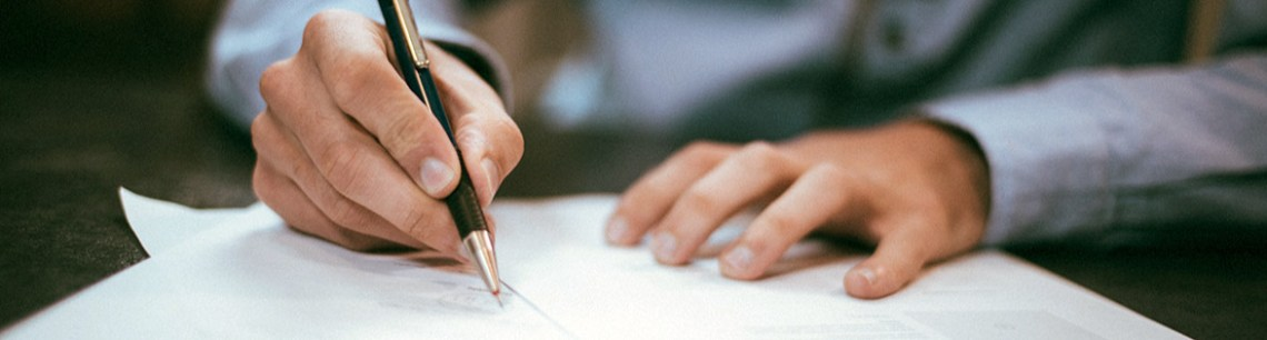 Photo of a man writing signing a contract