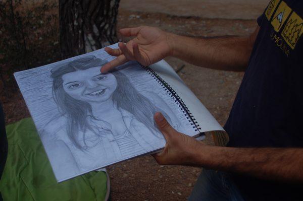 Dilgin displays a drawing of a girl. (Iris Samuels)