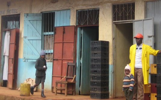 men and child on a street with furniture outside open doors