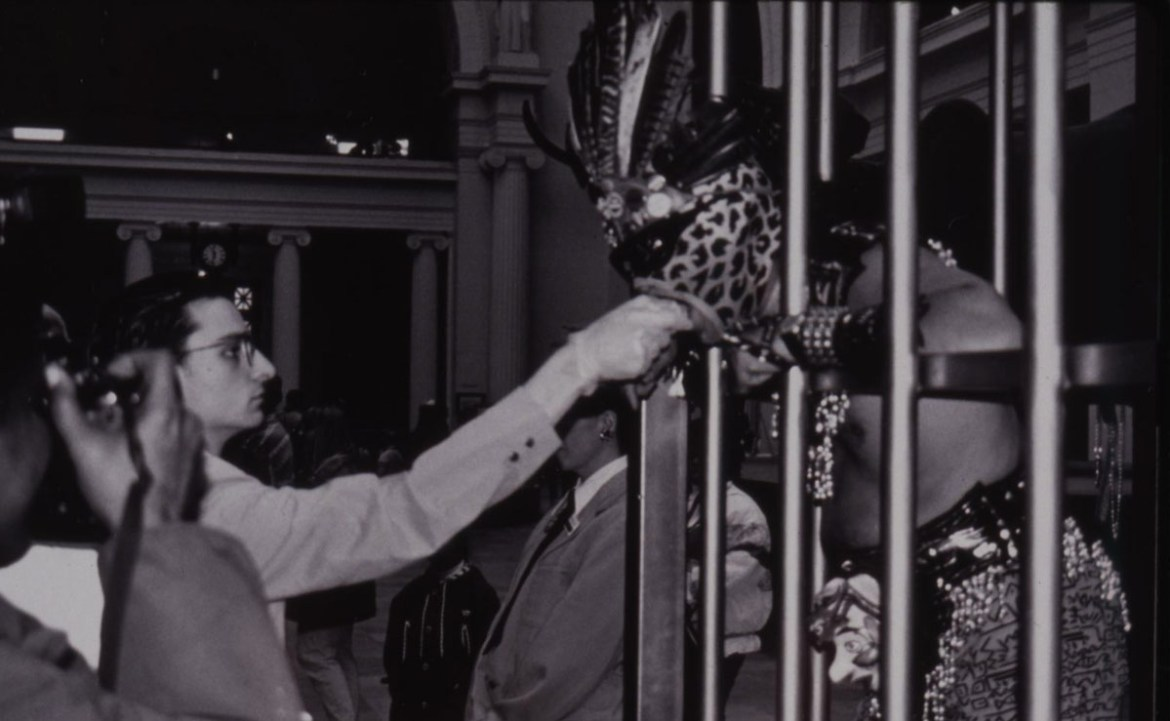 man feeding another man in a cage