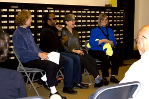 Picture shows from left to right, Project Manager Katherine Allen, Project Advisor Edery Herrera, Artist Teresa Jaynes, and Project Advisor Suzanne Erb, seated on grey folding chairs, in front of a card catalog. Allen, smiles and holds a sheet of paper in her lap. Hererra laughs, his left hand holding a tiny microphone near his mouth. Jaynes laughs wth her mouth open. Erb smiles and knits with a ball of yellow yarn under her right elbow. Parts of the backs of the heads and shouldPicture shows from left to right, Project Manager Katherine Allen, Project Advisor Edery Herrera, Artist Teresa Jaynes, and Project Advisor Suzanne Erb, seated on grey folding chairs, in front of a card catalog. Allen smiles and holds a sheet of paper in her lap. Hererra laughs, his left hand holding a tiny microphone near his mouth. Jaynes laughs with her mouth open. Erb smiles and knits a knitted square from a ball of yellow yarn tucked under her right elbow. Parts of the backs of the heads and shoulders of two audience members, separated by a chair, are visible in the foreground. [End of description]