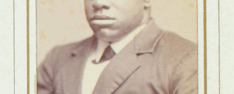 """Thomas Greene Bethune, known as Blind Tom, ca. 1870. Black & white photograph. 4 x 2.5 in. Picture depicts the carte-de-visite portrait photograph of musician Thomas Greene Bethune, later Wiggins, known as Blind Tom. Shows the young African American man from his waist up, his body slightly angled to the viewer's right. His tightly curled hair is shortly cropped. His eyes are closed. He wears a white shirt with a turned down collar. Under the collar is a dark cross tie. He also wears a dark jacket with wide notch lapels, several creases around the waist, and the top button fastened. The photograph is framed within a rectangular shape printed with a thick gold line surrounded by a thin black line. The frame is on light-colored paper. The top edge of the frame is slightly rounded. Hand written text below the portrait reads: """"Blind Tom"""" [End of description]"""