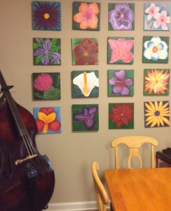 Picture shows the tan painted wall of a dining area decorated with a display of twelve flower paintings. Paintings are arranged in vertical and horizontal rows of four. A cello rests near the paintings in the lower left corner of the image. In the right, toward the viewer, is the upper corner of a rectangular light-colored wooden table. A light-colored wooden chair is placed at the head and the side of the table. [end of description]