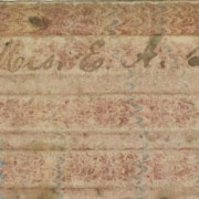 """Picture shows the upper edge of a writing board or tablet over a white background. The tablet is made of a brown cardboard-like material with a faded pink and blue marbled pattern and has raised, tactile, evenly spaced bars on its surface. In the center of the first bar, handwritten script reads """"Mrs. E. A. Lusk."""" [End of description]"""