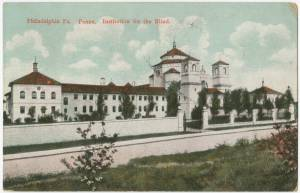 "Picture shows an elongated white multi-story building with a central tower and columns. Building contains red pitched roofs and several rectangular and curved-edged windows. Trees evenly line the property in front of the building. A fence made of white stone wall on the left, an open gate in the center, and metal pickets on the right also lines the property in front of the trees. Clouds hang in the sky above the building. A grass lawn and bushes with pink flowers are visible across the street from the school and in the foreground. Red text printed in the upper right corner reads: ""Philadelphia, Pa. Penna. Institution for the Blind."" [End of description]."