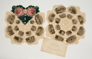 """Picture shows two flower-shaped prints of """"eight petals"""" illustrated with vignettes of buildings, landscape views, and portraits arranged in a circle of images nested within an outer circle of images. Very tiny rectangular and triangular shaped cut-outs line the open folds of the print. The jagged-edged prints are accompanied by an envelope printed in cursive letters in red ink reading: """"Rose of Philadelphia."""" The print in the left also contains two images of a pink rose bud with green petals as """"petals"""" on its upper edge. [End of description]"""