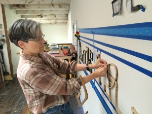Picture shows Teresa Jaynes at work in her studio. Jaynes stands to the viewer's left. She looks at her hands as she adjusts a large-size, wooden sculptural letter between lines of blue tape on a white wall.
