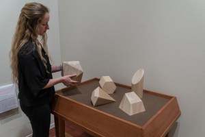 Picture shows a woman, in the far left, holding one of five differently-shaped wooden geometric forms that rest on a wooden table. The top is covered in brown linen. Shapes include a trapezoid, trapezium, octagon, slant and flat-edged cylinder, and prism. The woman wears a black shirt and pants, and has her long blond hair pulled slightly away from her face.
