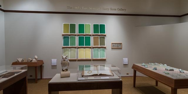 Picture shows the majority of the gallery, including four of Jaynes's seven installations on view. In the center foreground is Jaynes's Gift#1 on display on a flat, horizantally-angled rectangular table with a dark wood base. A white and brown paper maiche owl rests on a cylindrical stand to the left of a large open book under a rectangular, clear acrylic hood. To the right of the display with the owl stands Jayne's Gift #5, a map represention of the travels of the 19th–century blind surveyor John Metcalf. It is a vertically-positioned, large rectangular table composed of a a padded linen top and a light brown wood base. A multi-color grid, outlines of geometric shapes, and green porcelain geometric forms adorn the linen top. To the left of the owl display is a partial view of a case of historical materials. In the left backround is Jayne's Gift #3 inspired by the mathematical tools of the blind mathematician Nicholas Saunderson. It is a light brown table on which several large-sized wooden geometric shapes of different styles rest. In the center background, on the back wall painted off-white, is Jayne's Gift #4, a visual transmutation after the musical work of blind African Amerian musician Thomas Wiggins. It is three horizontal and three vertical rows of prints in a geometric interplay of greens, browns and yellows. To the right of the prints on the wall is a small wooden frame in which brass musical notes are displayed. To the far right background is a partial view of an off-white curved wall. The floor of the room is covered with a tan colored carpet.