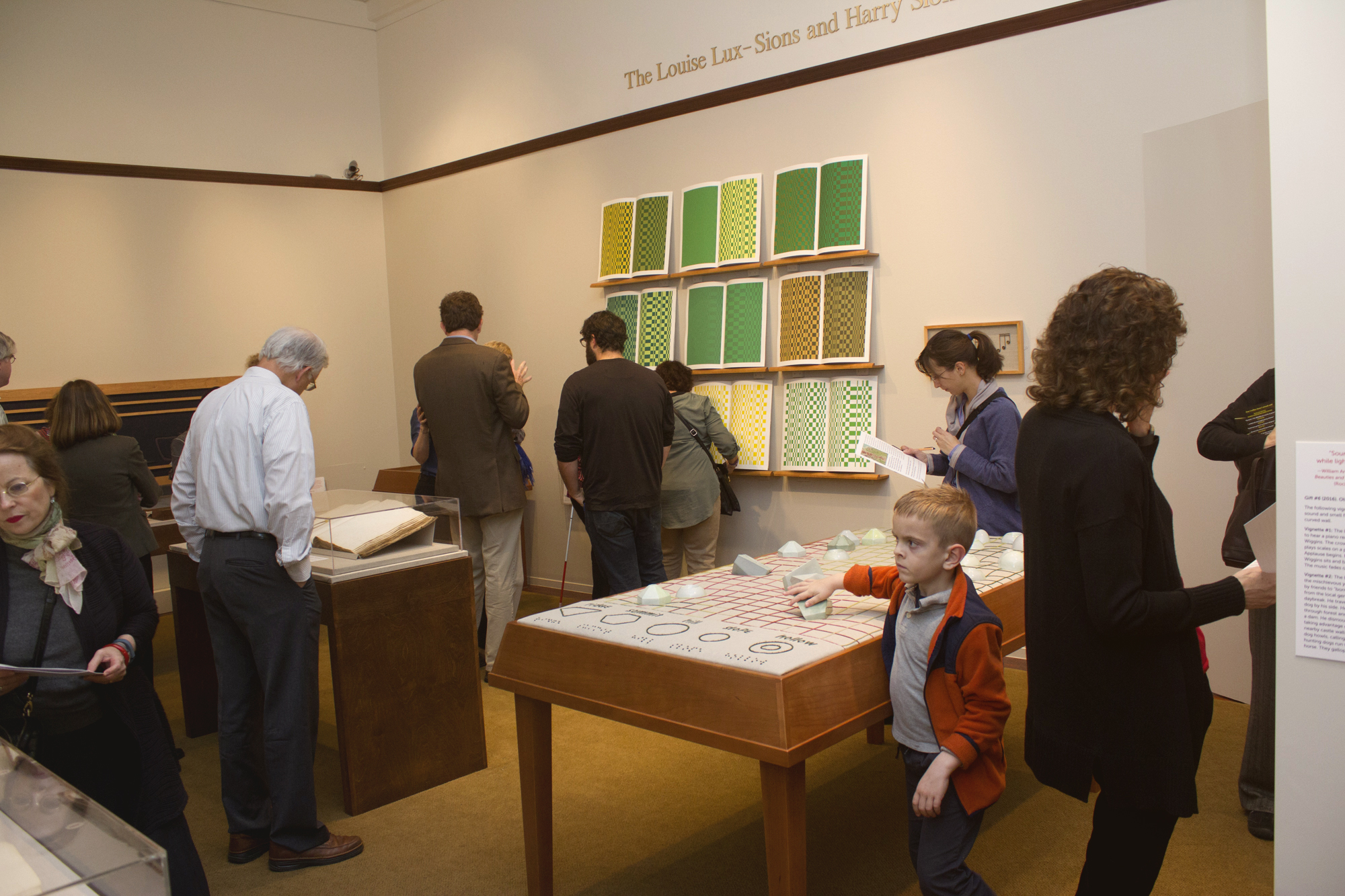 Picture shows several visitors, including a young boy, touching and viewing the installations in the center and east wall of the gallery. In the far left is a large book under a clear, mylar hood in a display case. In the left is Jayne's Gift #5, a map representation of the travels the 19th–century blind surveyor John Metcalf. It is a vertically-positioned, large rectangular table composed of a linen top and a light brown wood base. A multi-color grid, outlines of geometric shapes, and green porcelain geometric shapes adorn the linen top. In the center background, on the back wall painted off-white, is Jayne's Gift #4, a visual transmutation after the musical work of blind African American musician Thomas Wiggins. It is three horizontal and three vertical rows of prints in a geometric interplay of greens, browns and yellows. [end of description]