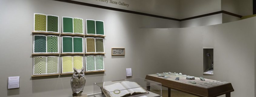 Picture shows the gallery, including four of Jaynes's seven installations on view. In the center foreground is Jaynes's Gift#1 on display on a flat, horizontally-angled rectangular table with a dark wood base. A white and brown paper owl rests on a cylindrical stand to the left of a large open book under a rectangular, clear acrylic hood. To the right of the display with the owl stands Jayne's Gift #5, a map representation of the travels the 19th–century blind surveyor John Metcalf. It is a vertically-positioned, large rectangular table composed of a a linen top and a light brown wood base. A multi-color grid, outlines of geometric shapes, and green porcelain geometric shapes adorn the linen top. In the center background, on the back wall painted off-white, is Jayne's Gift #4, a visual transmutation after the musical work of blind African American musician Thomas Wiggins. It is three horizontal and three vertical rows of prints in a geometric interplay of greens, browns and yellows. To the right of the prints on the wall is a small wooden frame in which brass musical notes are displayed. To the far right background is a view of Jaynes's Gift #6, the scent mechanism the olfactometer, in a niche in an off-white curved wall. The floor of the room is covered with a tan colored carpet. [end of description]