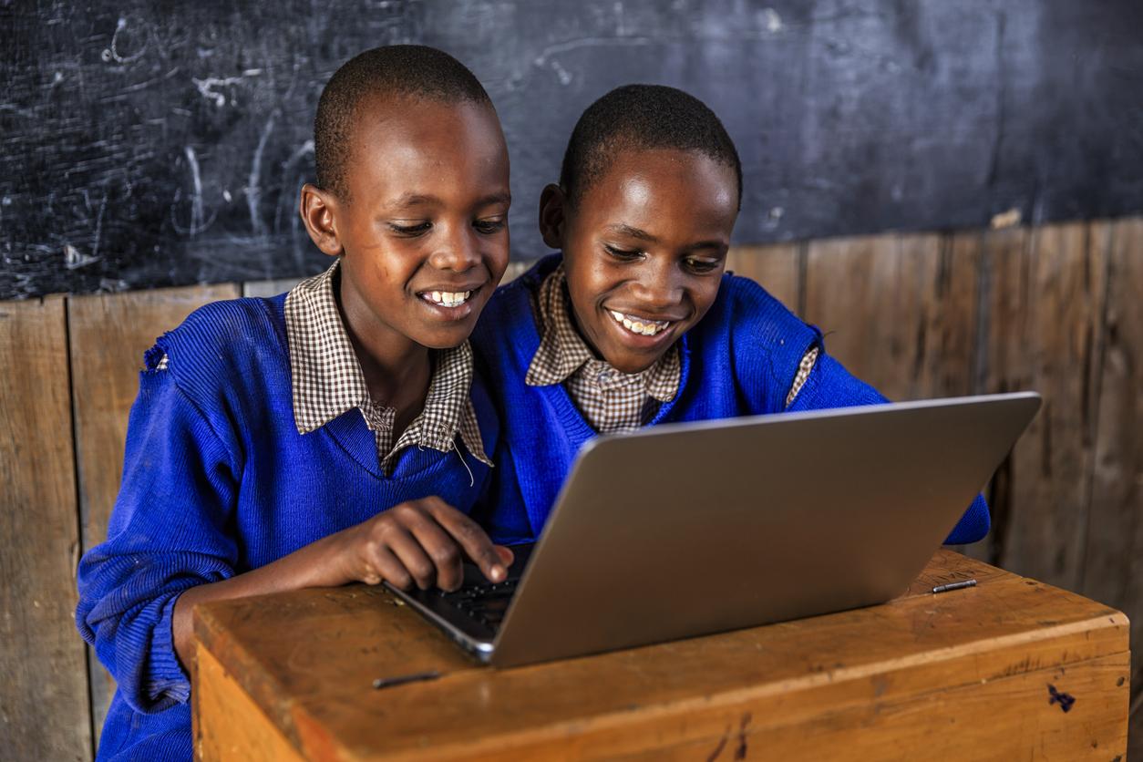 Kenyan children using a laptop inside classroom, Kenya
