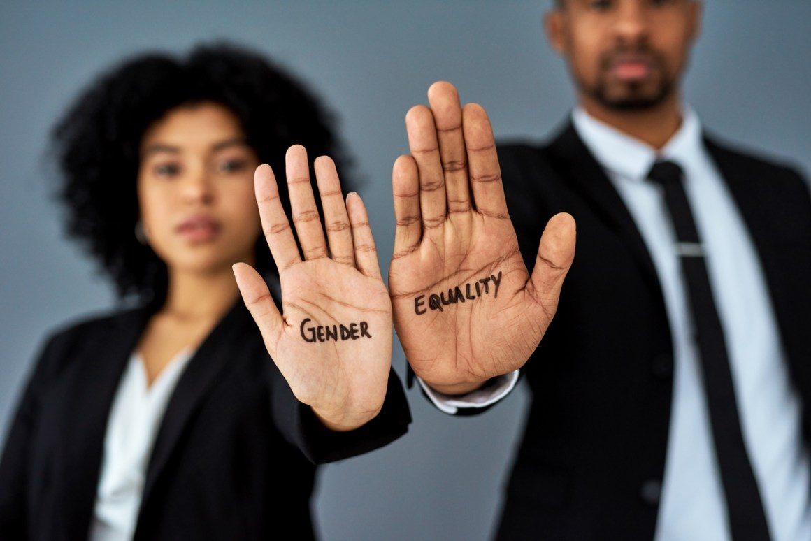 Shot of businessman and businesswoman advocating for gender equality against a grey studio background