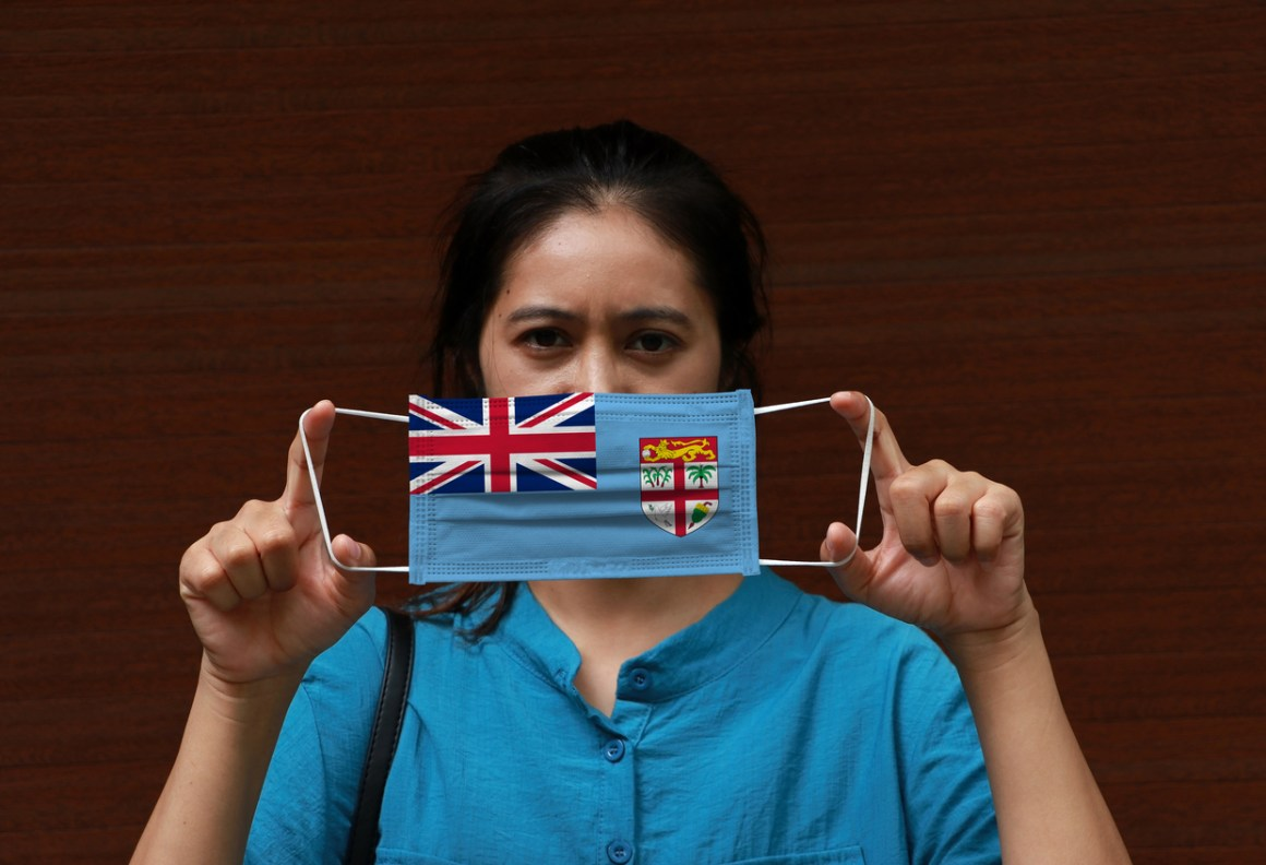 A woman with Fiji flag on hygienic mask in her hand and lifted up the front face on brown background. COVID-19 Fiji testing kits