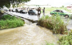 Scenic view of the burstling of the heavily flooded culvert at FUNAAB end of Alabata / Camp Road